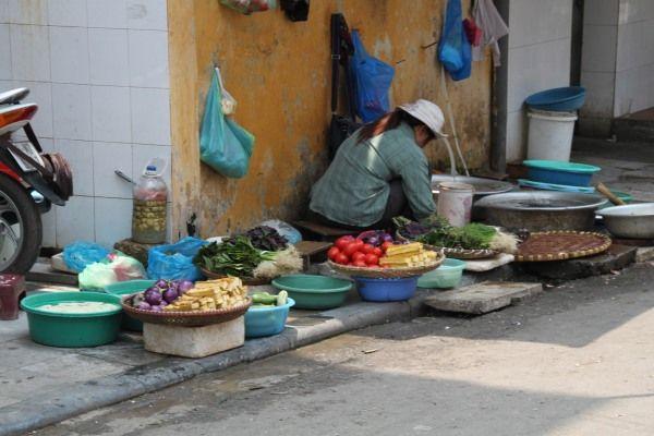 Verkäuferin auf einem traditionellem Straßenmarkt in Hanoi